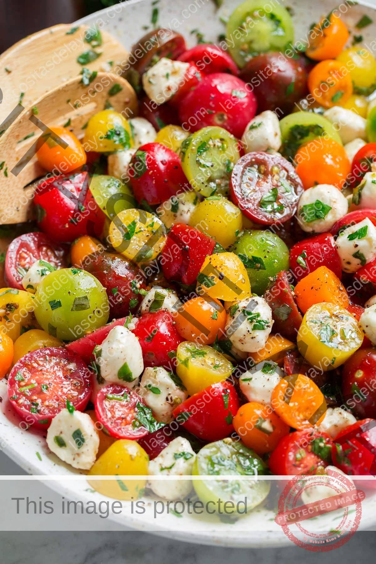 Imagen que muestra ensalada de tomate desde un ángulo lateral en un tazón para servir.