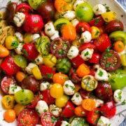 Ensalada de tomate en un cuenco blanco. En la ensalada hay tomates cherry y uva multicolores, las perlas de mozzarella y se cubre con un aderezo de hierbas.