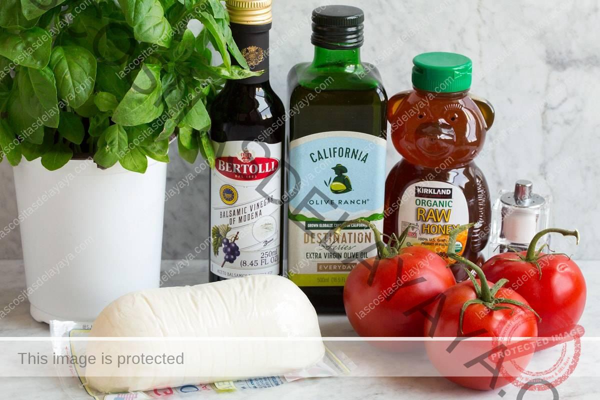 Ingredientes de la ensalada Caprese que se muestran en esta imagen.  Incluye mozzarella fresca, albahaca fresca, tomates frescos, aceite de oliva, miel, vinagre balsámico, sal y pimienta.