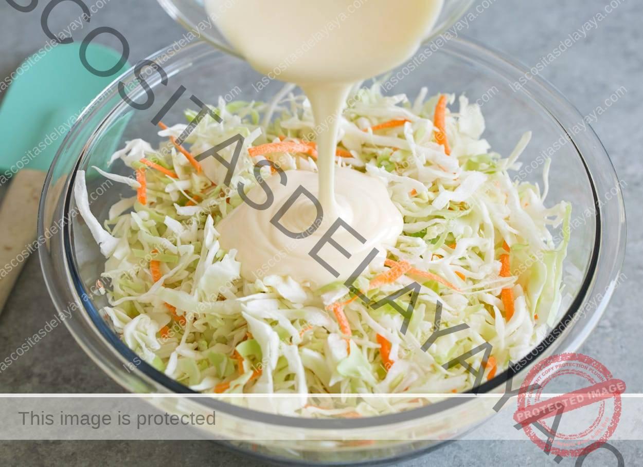 Agregue el aderezo de ensalada de col a la ensalada de col en el tazón.