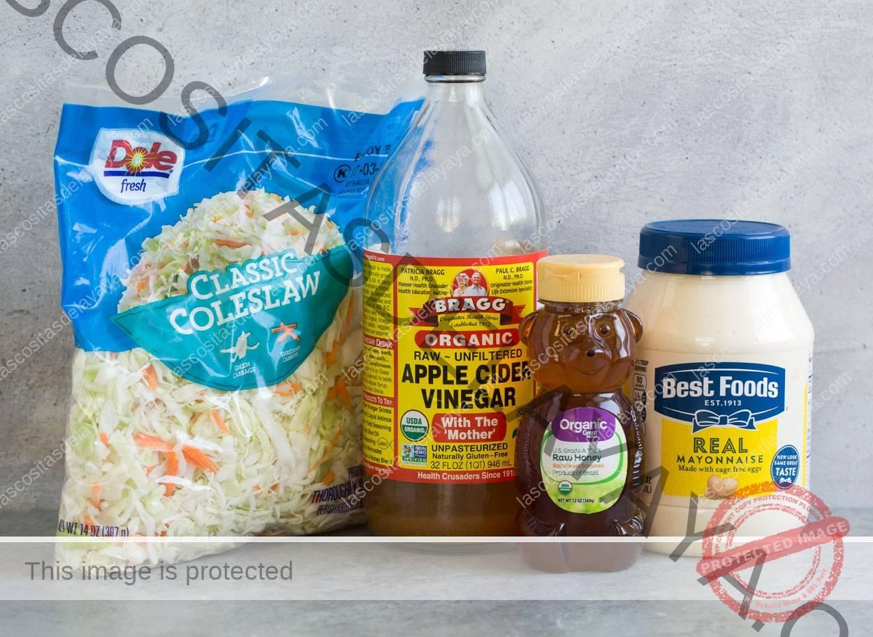 Los ingredientes de la ensalada de col se muestran aquí, incluida la mayonesa, la miel, el vinagre de sidra de manzana y la mezcla de ensalada de col.