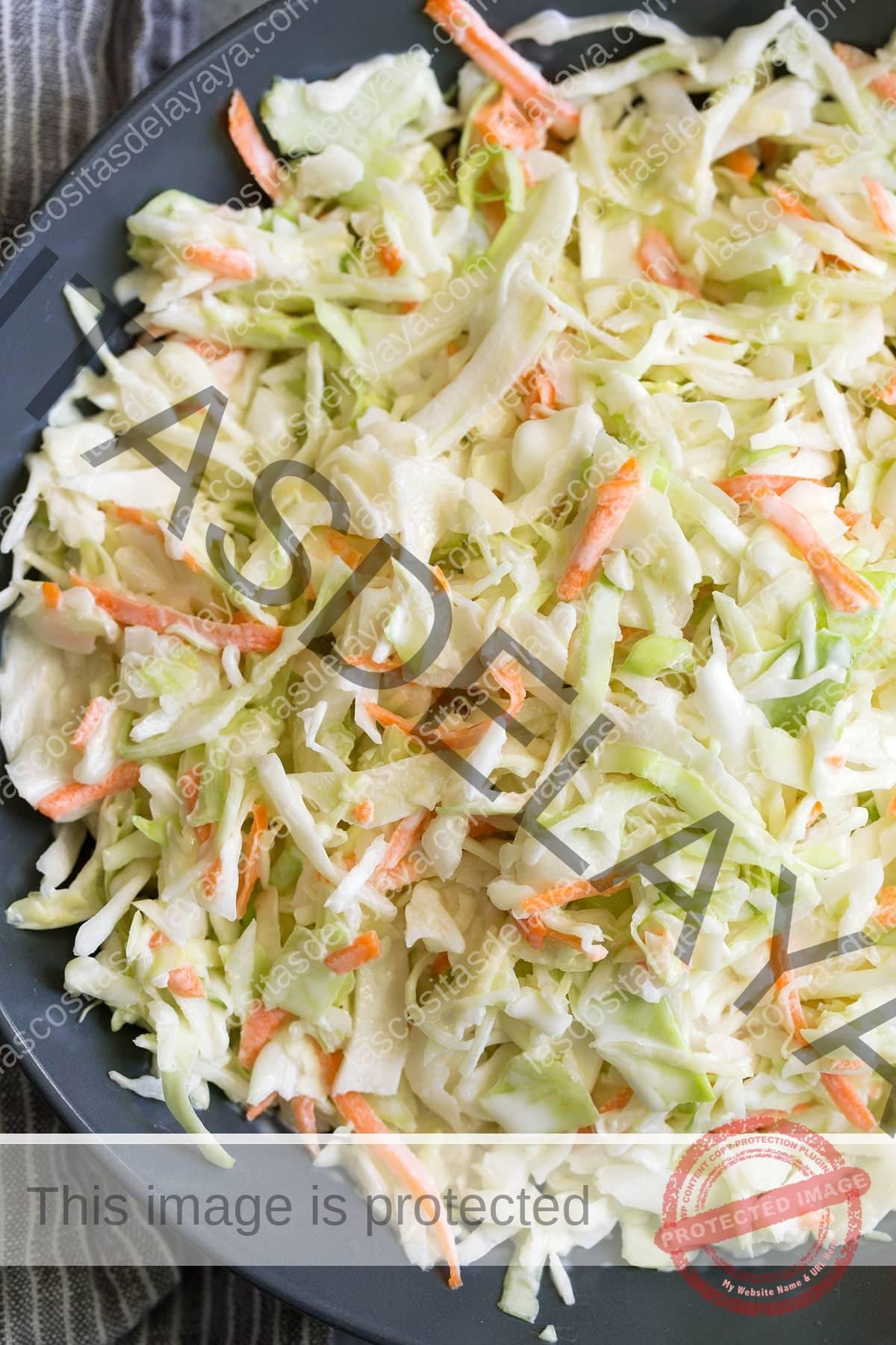 Cerrar imagen de ensalada de col con aderezo en un recipiente azul oscuro.