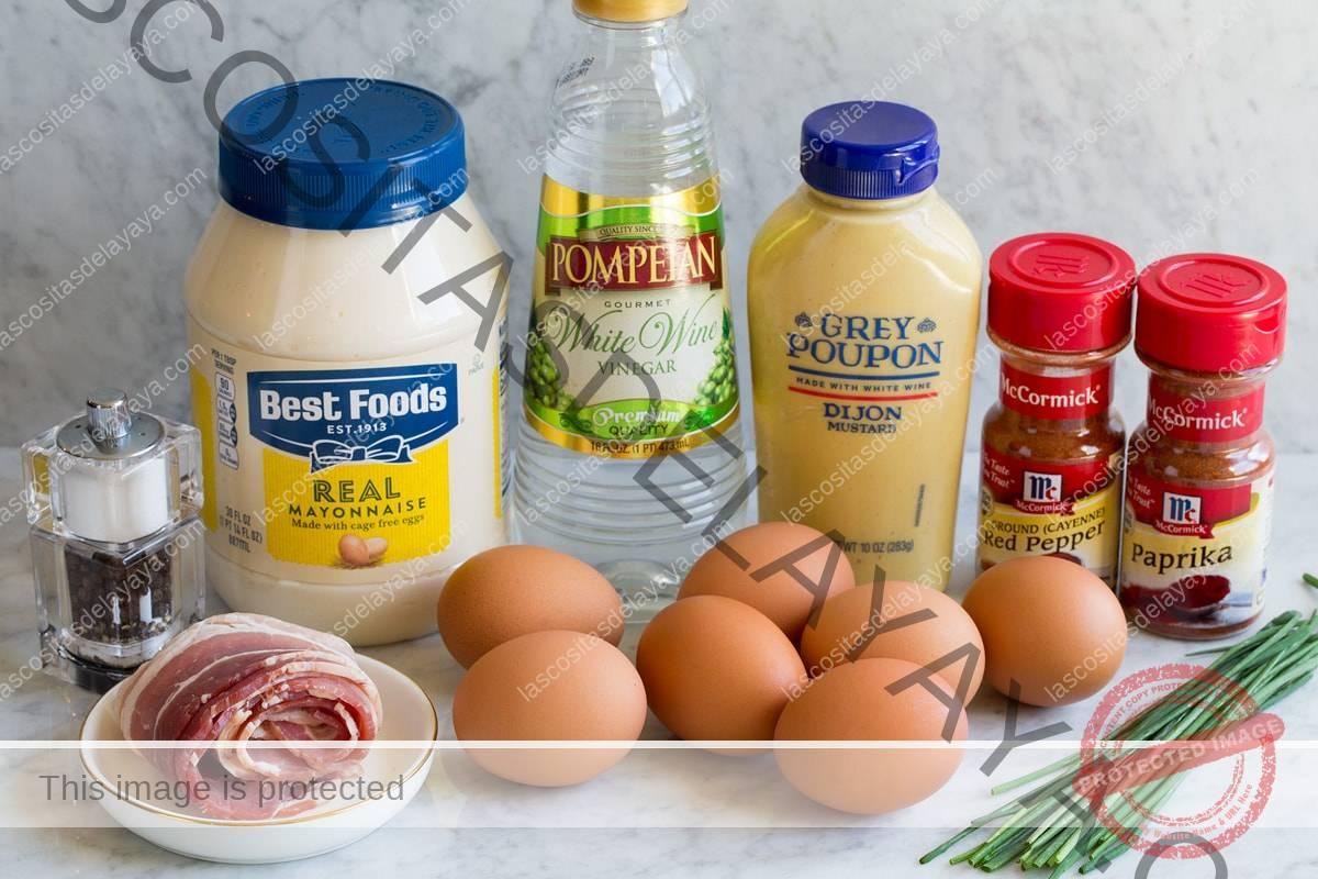 Imagen que muestra los ingredientes que se encuentran en los huevos duros, que incluyen mayonesa, mostaza dijon, vinagre de vino blanco, huevos, cebolletas, pimienta de cayena, pimentón, cebollino y tocino.