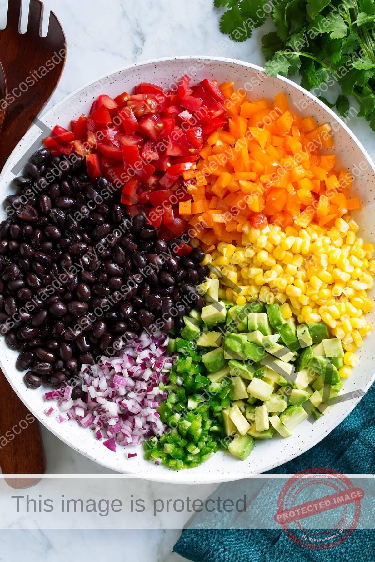 Ingredientes de ensalada de maíz y frijoles negros en un tazón antes de mezclar.