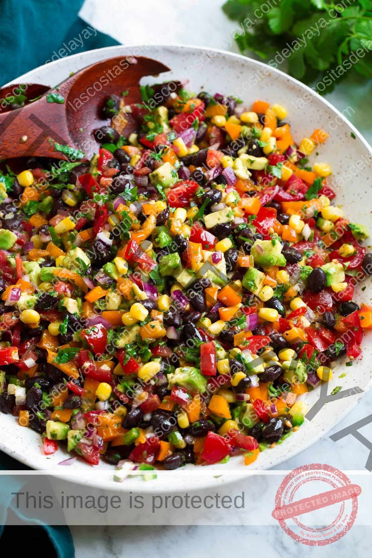 Ensalada de frijoles negros y maíz en una ensaladera blanca con cucharas de madera.