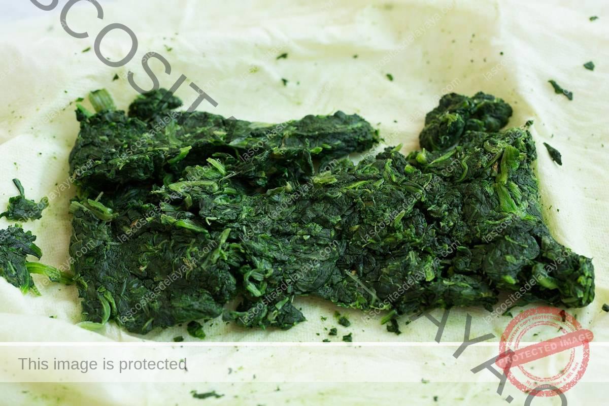 Se muestran espinacas en toallas de papel después de exprimir el exceso de humedad.  El primer paso para hacer champiñones rellenos.