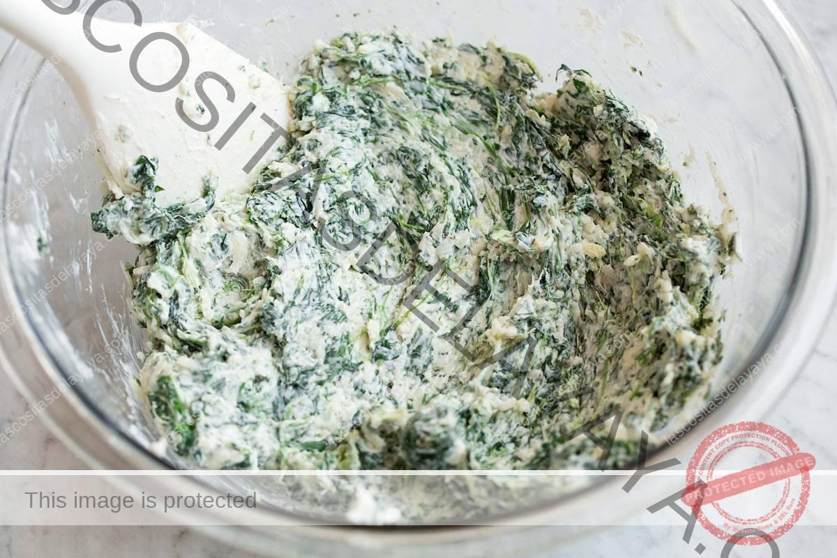 Relleno de champiñones rellenos que se muestra después de mezclarlos en el recipiente de vidrio.