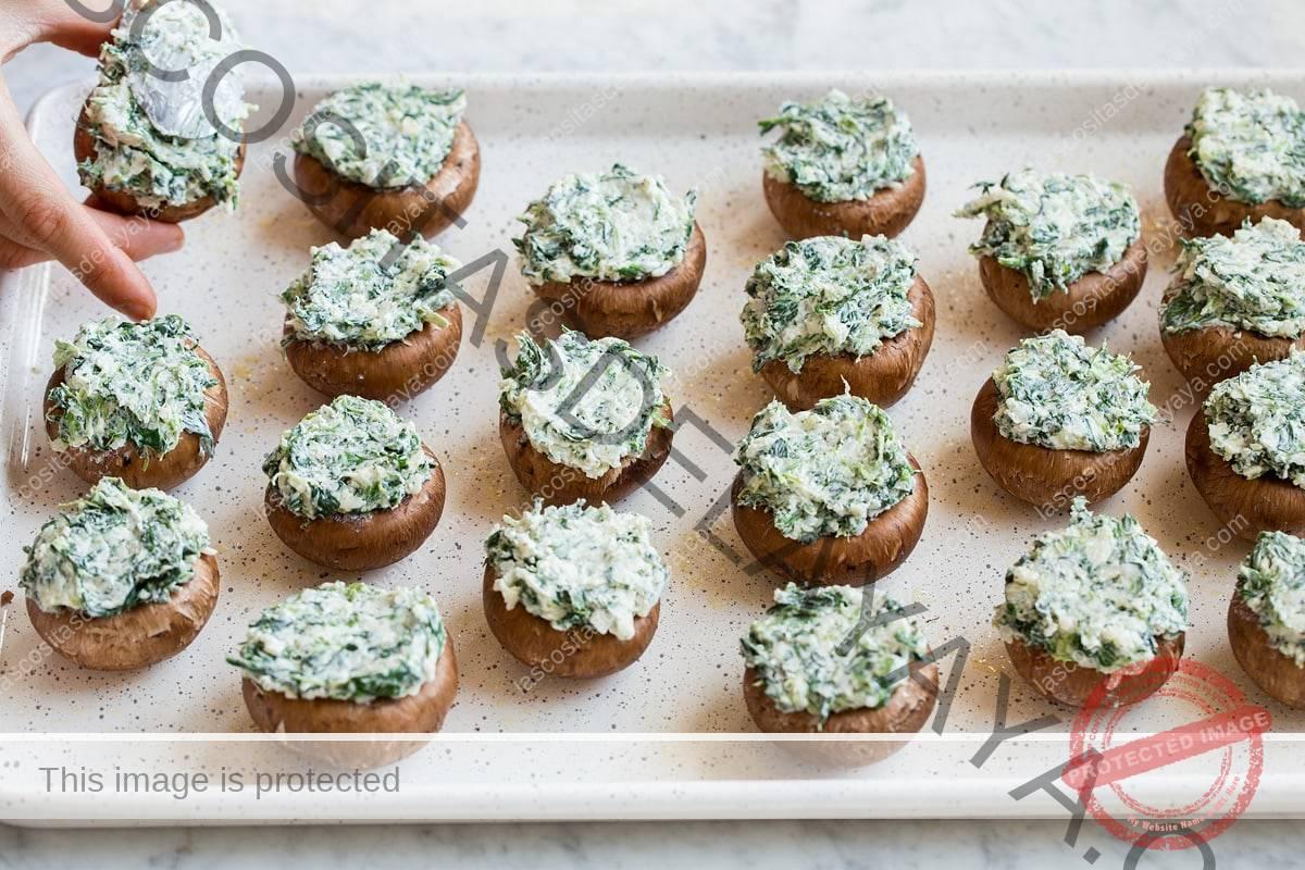 Llenar las tapas de champiñones con relleno de queso.
