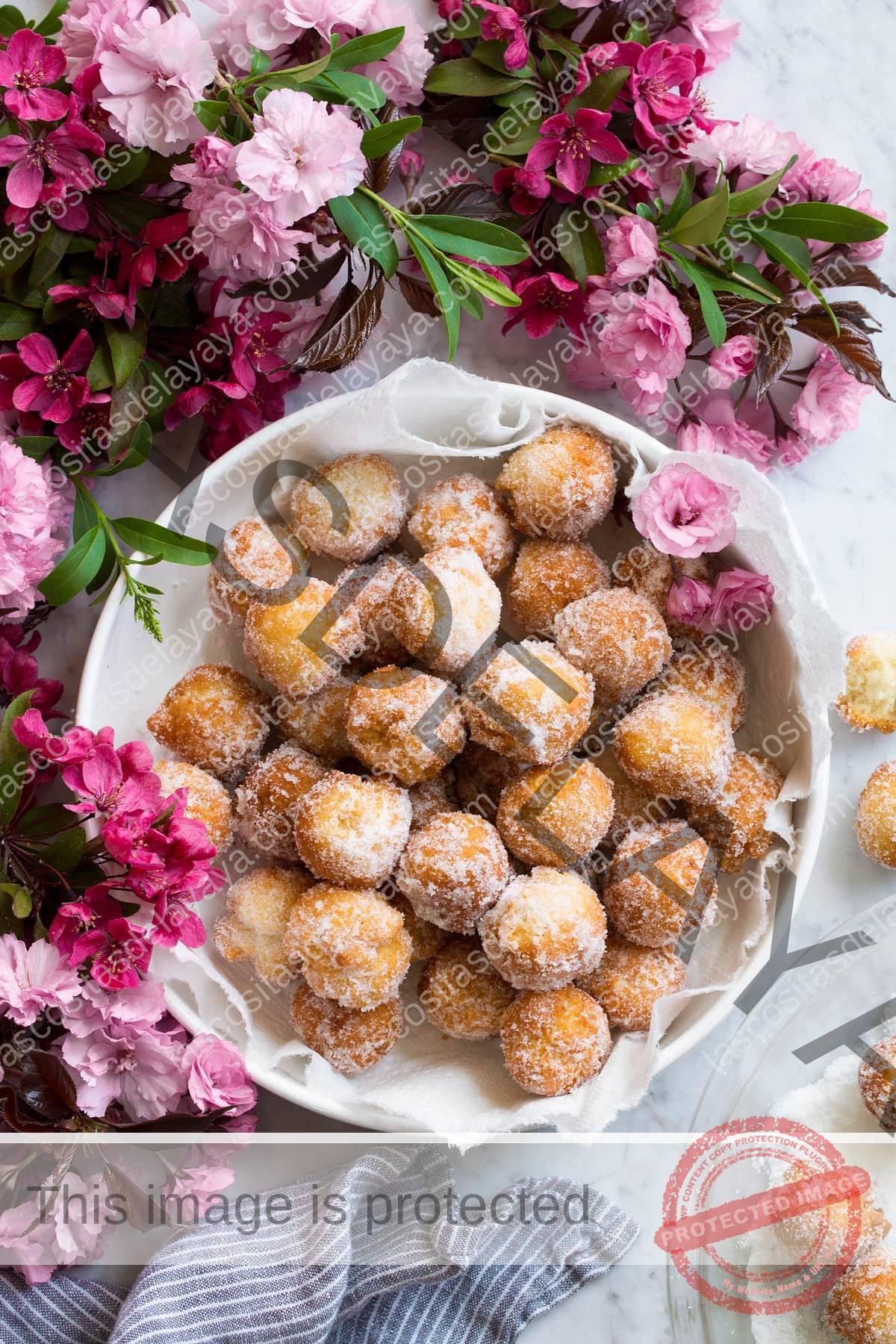 Donut agujeros en un cuenco rodeado de flores.