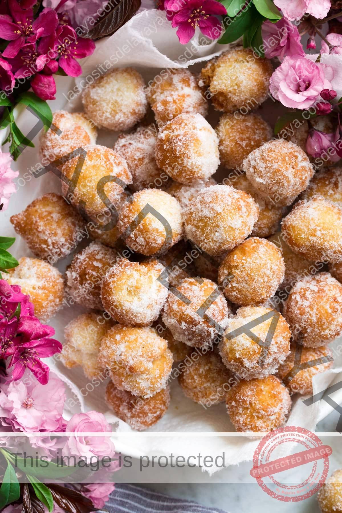 Cuenco lleno de agujeros de rosquilla cubiertos de azúcar y canela fresca.