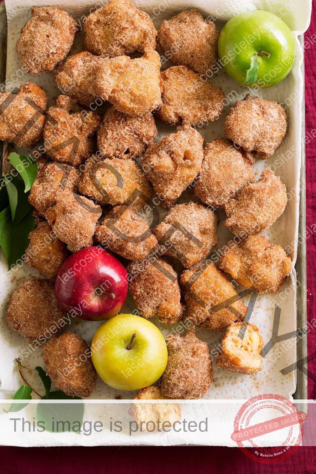 Muffins de manzana en una bandeja para hornear cubierta con una toalla de papel.