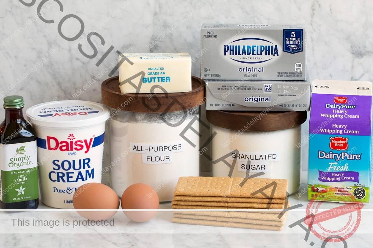 Imagen de los ingredientes utilizados para hacer mini tartas de queso.  Incluye queso crema, azúcar granulada, harina de trigo, huevos, galletas, crema agria, crema agria, vainilla y mantequilla.