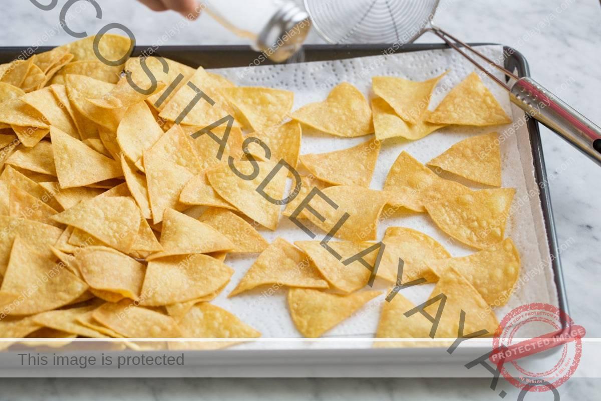 Escurre las tortillas fritas en una bandeja para hornear forrada con toallas de papel.