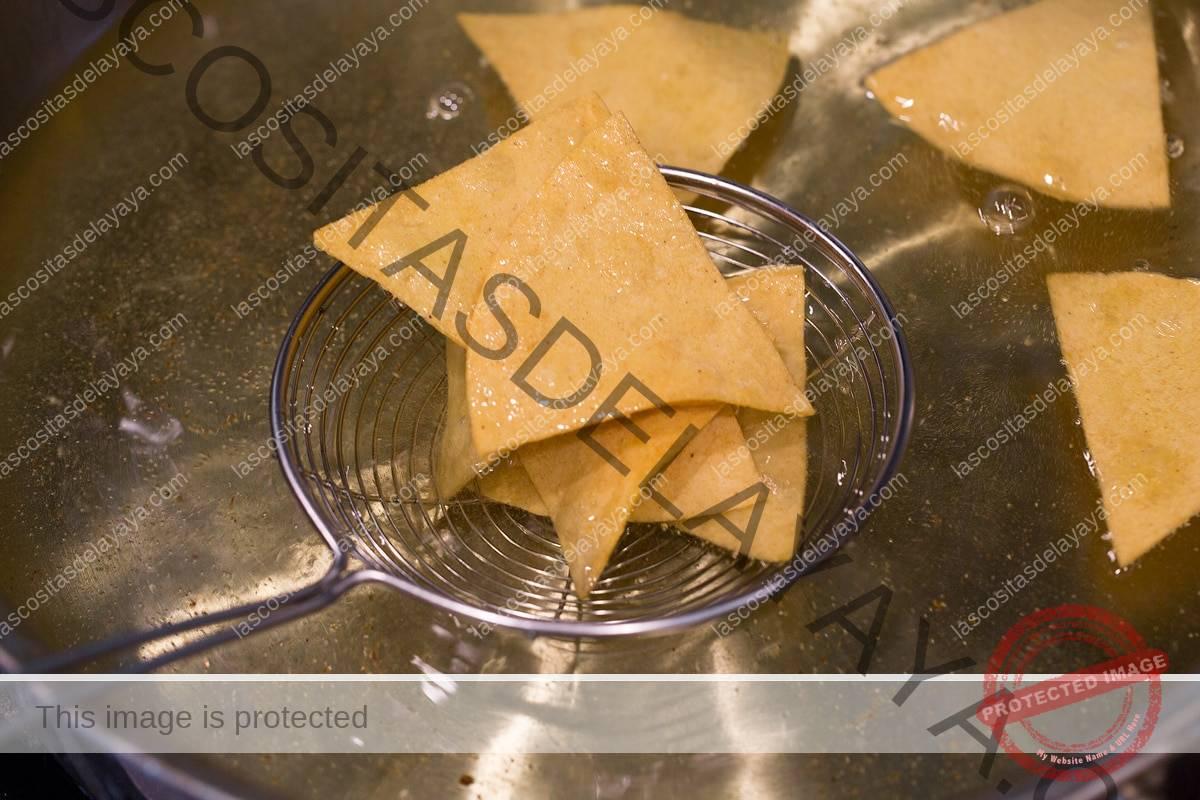 Escurrir los chips de tortilla con una araña de alambre.