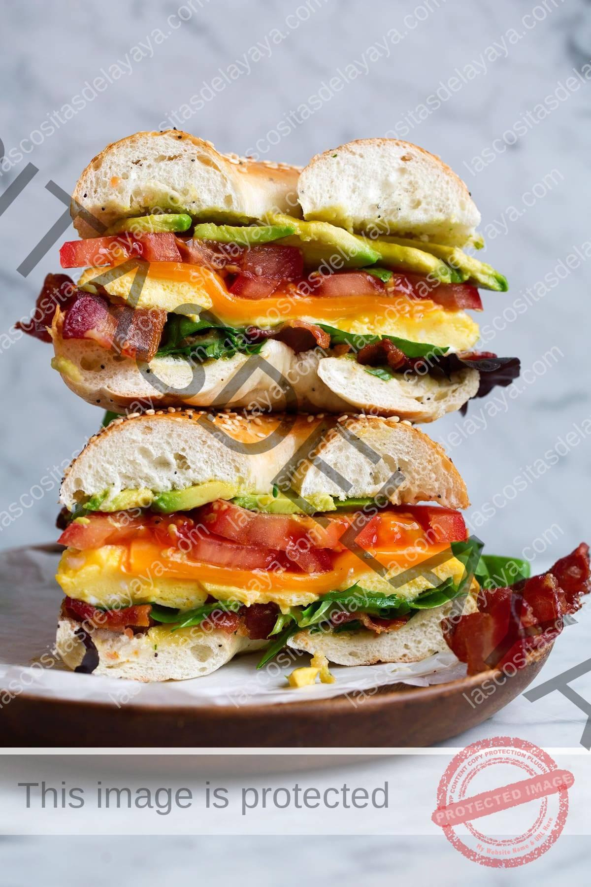 Sándwich de bagel con huevos para microondas, tocino, aguacate, tomate, queso cheddar y lechuga.  El sándwich se corta por la mitad y se apila sobre una tabla de madera sobre una superficie de mármol.