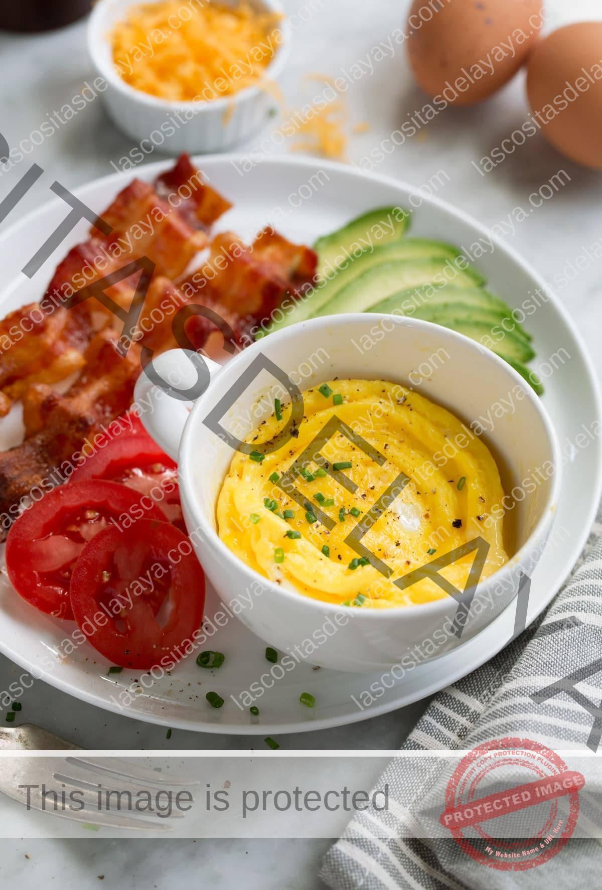 Cocine en el microondas los huevos con tocino, tomates y aguacate a un lado en un plato.