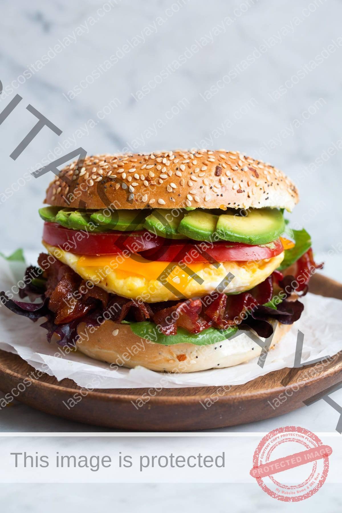 Sándwich de bagel con huevos para microondas, tocino, aguacate, tomate, queso cheddar y lechuga.