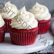 Se muestra glaseado de queso crema encima de los cupcakes de terciopelo rojo.
