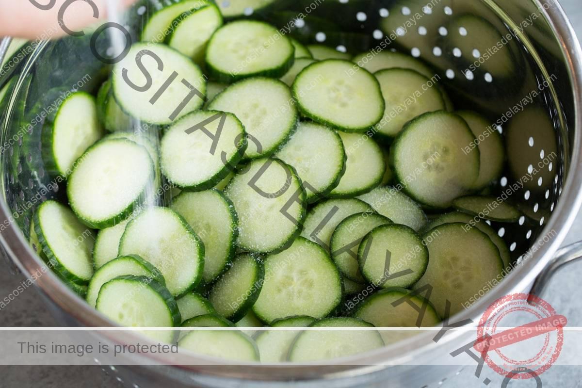 Mostrando cómo hacer ensalada de pepino.  Echar pepinos en un colador con sal.