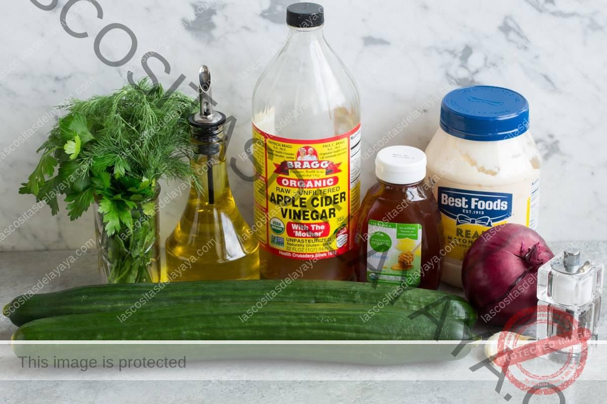 Los ingredientes necesarios para hacer la ensalada de pepino que se muestran aquí, incluyen pepinos ingleses, mayonesa, aceite de oliva, ajo, vinagre de sidra de manzana, eneldo, perejil, miel y cebolla morada.
