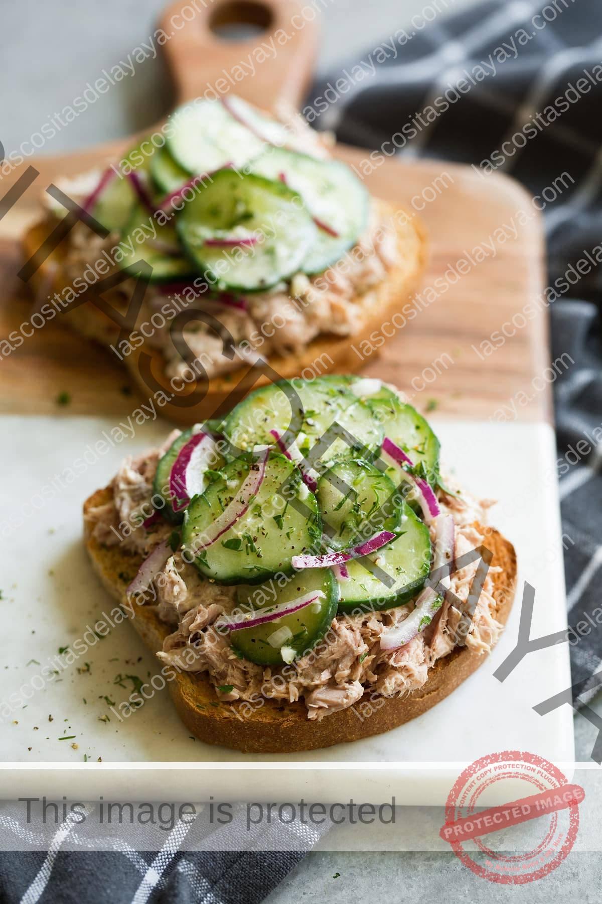 Ensalada de pepino servida sobre un sándwich de ensalada de atún abierto.  Servido con una guarnición de papas fritas.  Esta es una sugerencia de servicio.