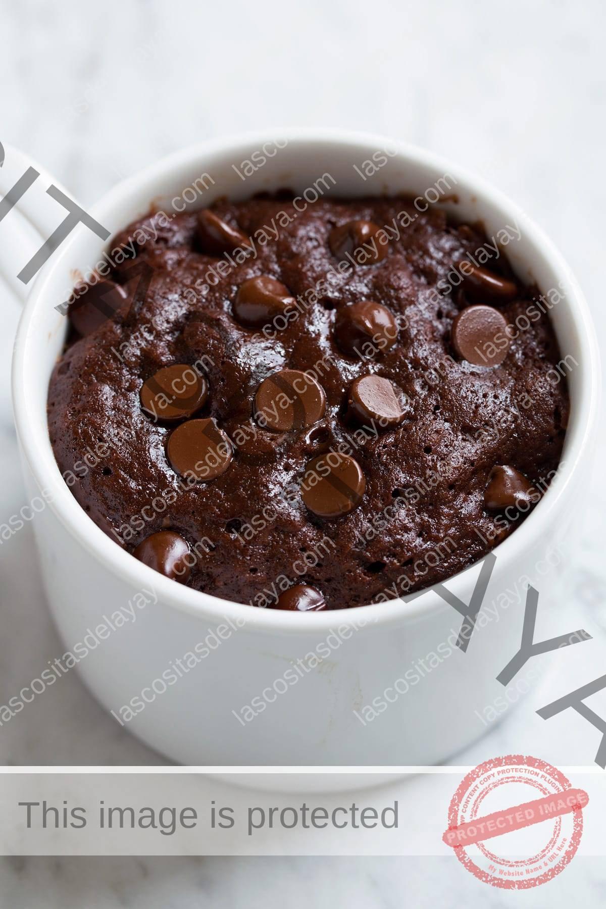 Pastel de taza de chocolate que se muestra justo después de cocinarlo en el microondas.
