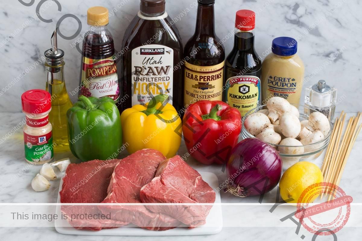 Los ingredientes necesarios para hacer barbacoas de carne que se muestran aquí, incluyen filetes, pimientos, cebolla morada, ajo, limón, mostaza de Dijon, salsa de soja, Worcestershire, miel, vinagre de vino tinto, aceite de oliva, ajo en polvo.