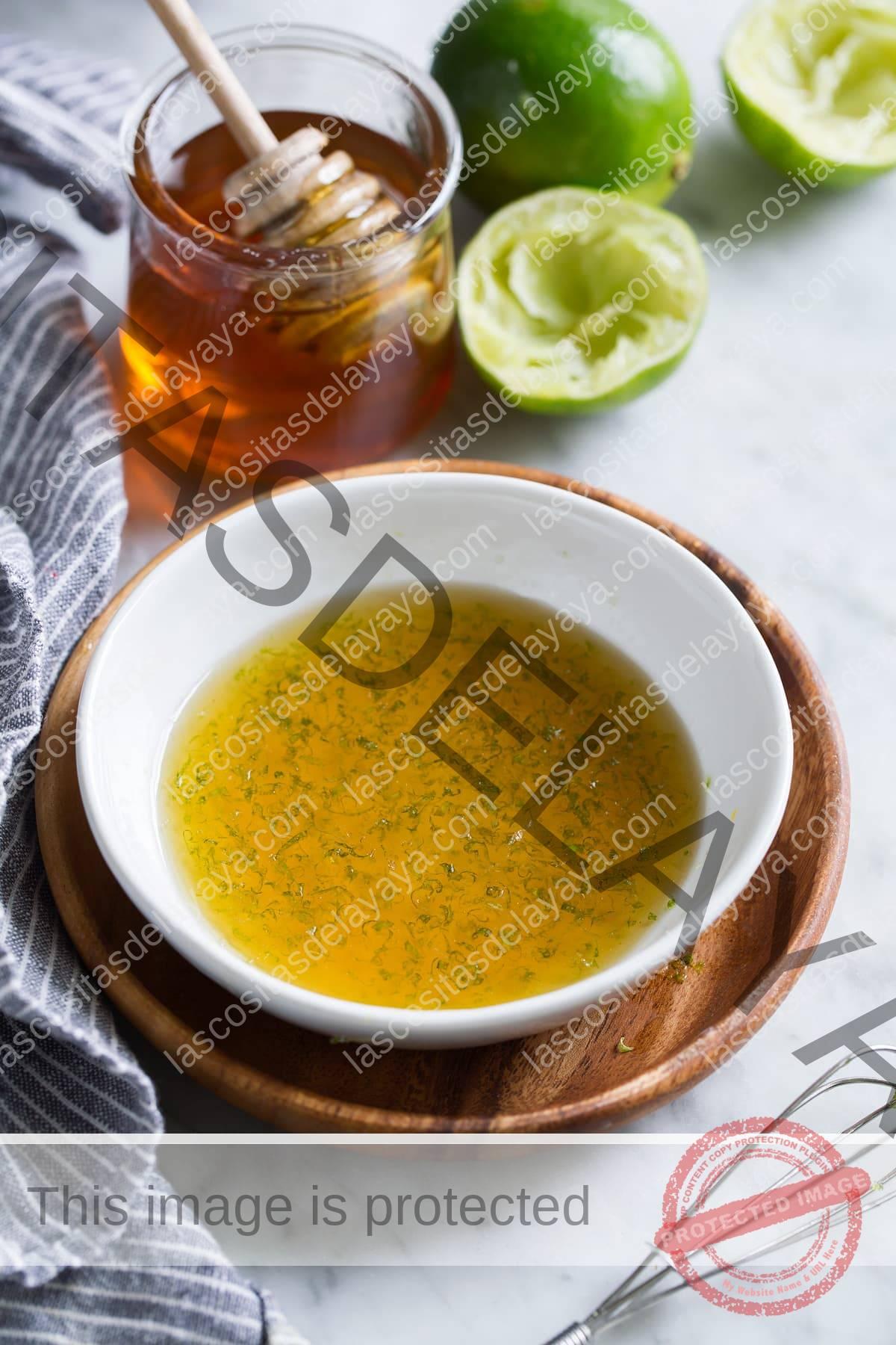 Aderezo de ensalada de frutas con miel y limón en un pequeño recipiente blanco sobre una placa de madera.