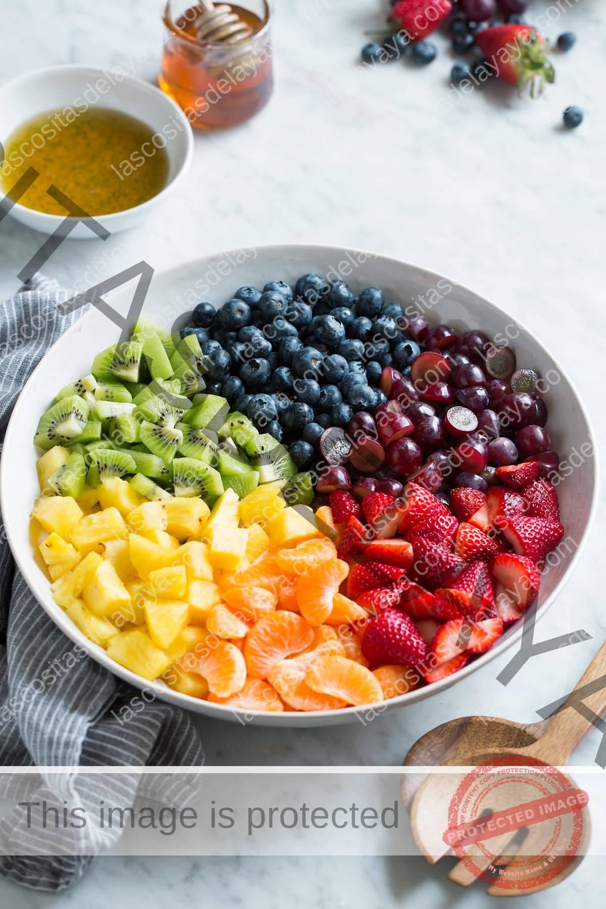 Fresas frescas, mandarina, piña, kiwi, arándano y uvas en secciones en un tazón blanco grande.