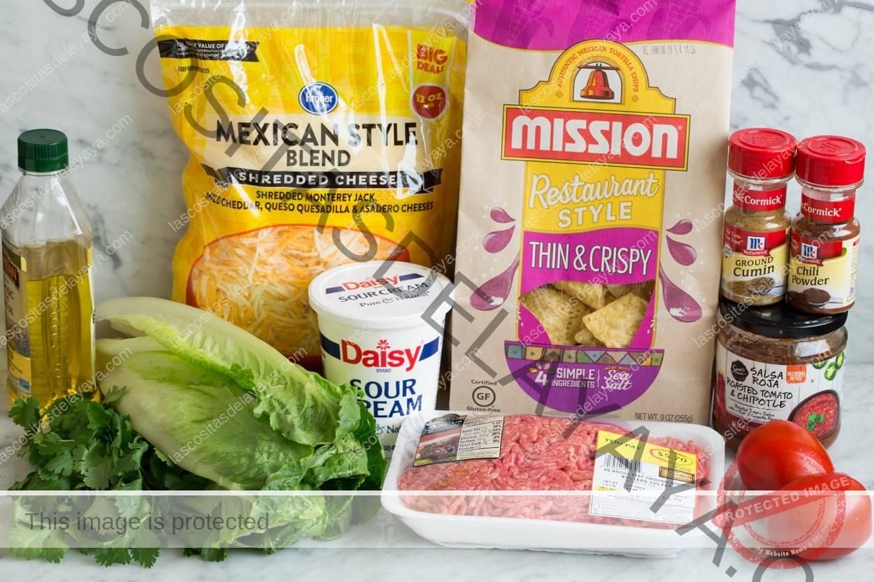 Imagen que muestra los ingredientes necesarios para la ensalada de tacos, que incluyen carne molida, aceite de oliva, especias, aderezo embotellado, papas fritas, queso, crema agria y tomates.