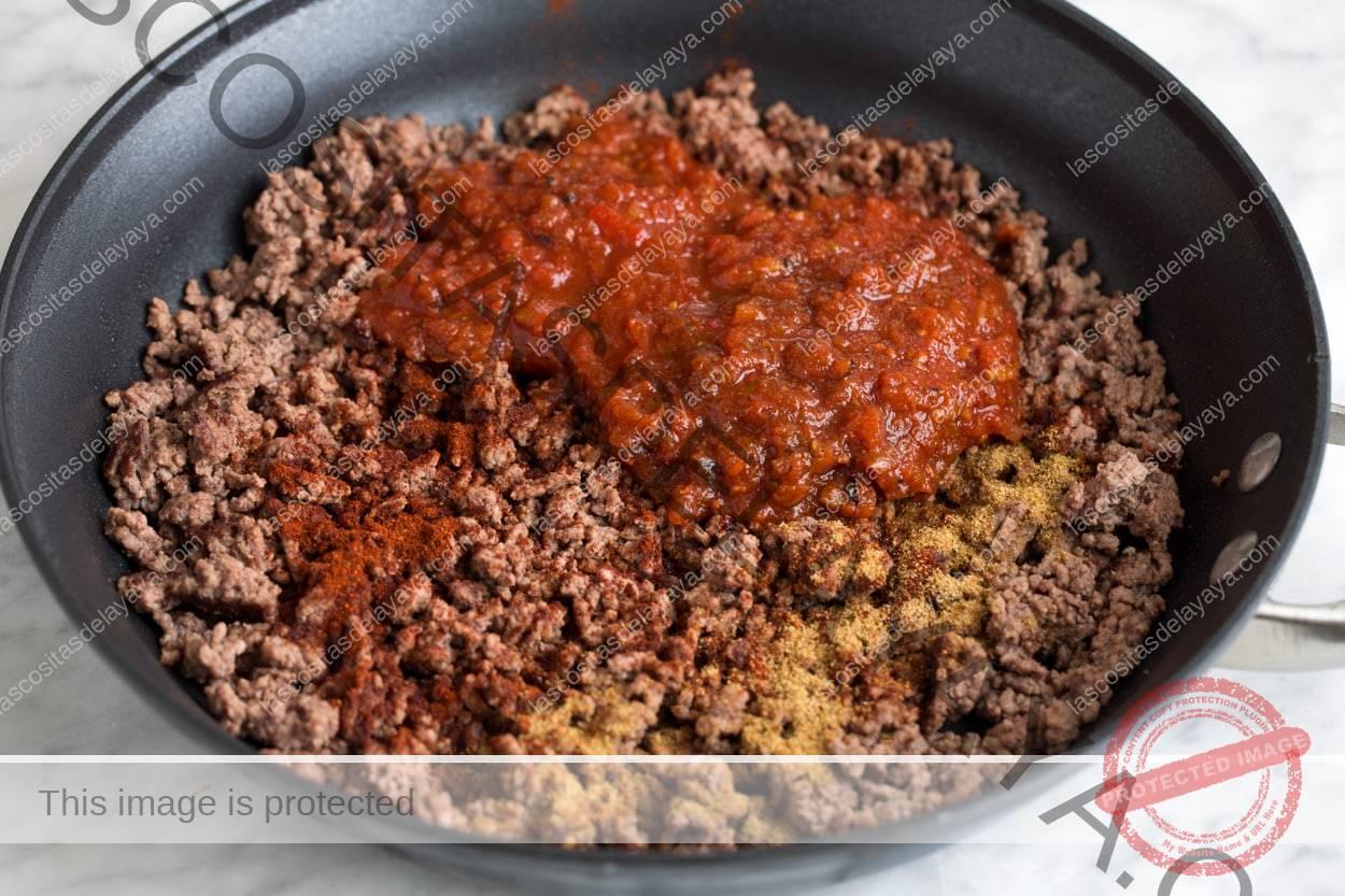 Agregue salsa y especias a la mezcla de carne molida cocida en una sartén grande.