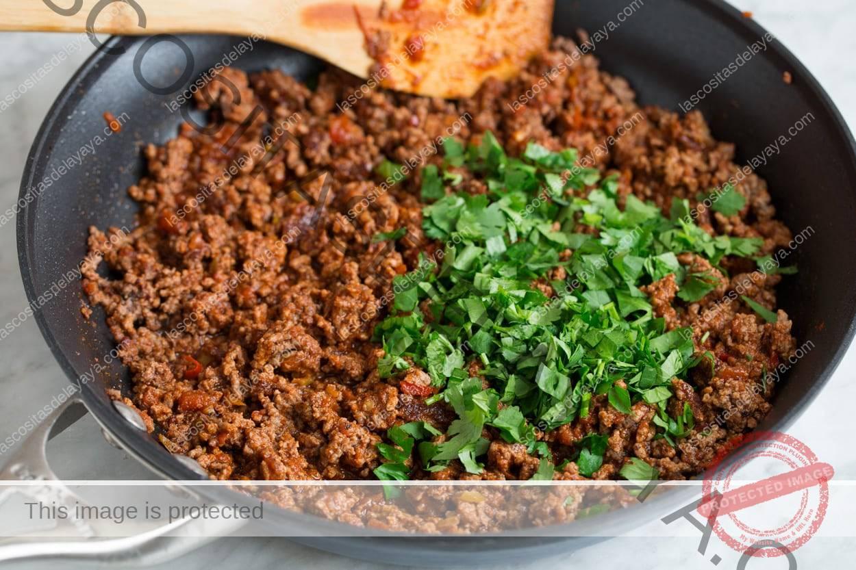 Agregue cilantro a la mezcla de carne y termine la ensalada de tacos en la sartén.