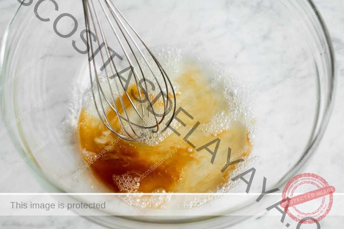 Mezcle la clara de huevo y el extracto de vainilla con un batidor en un bol de vidrio.