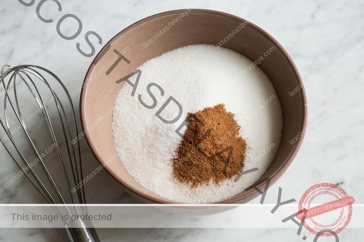 Mezclar el azúcar y la canela en un bol.