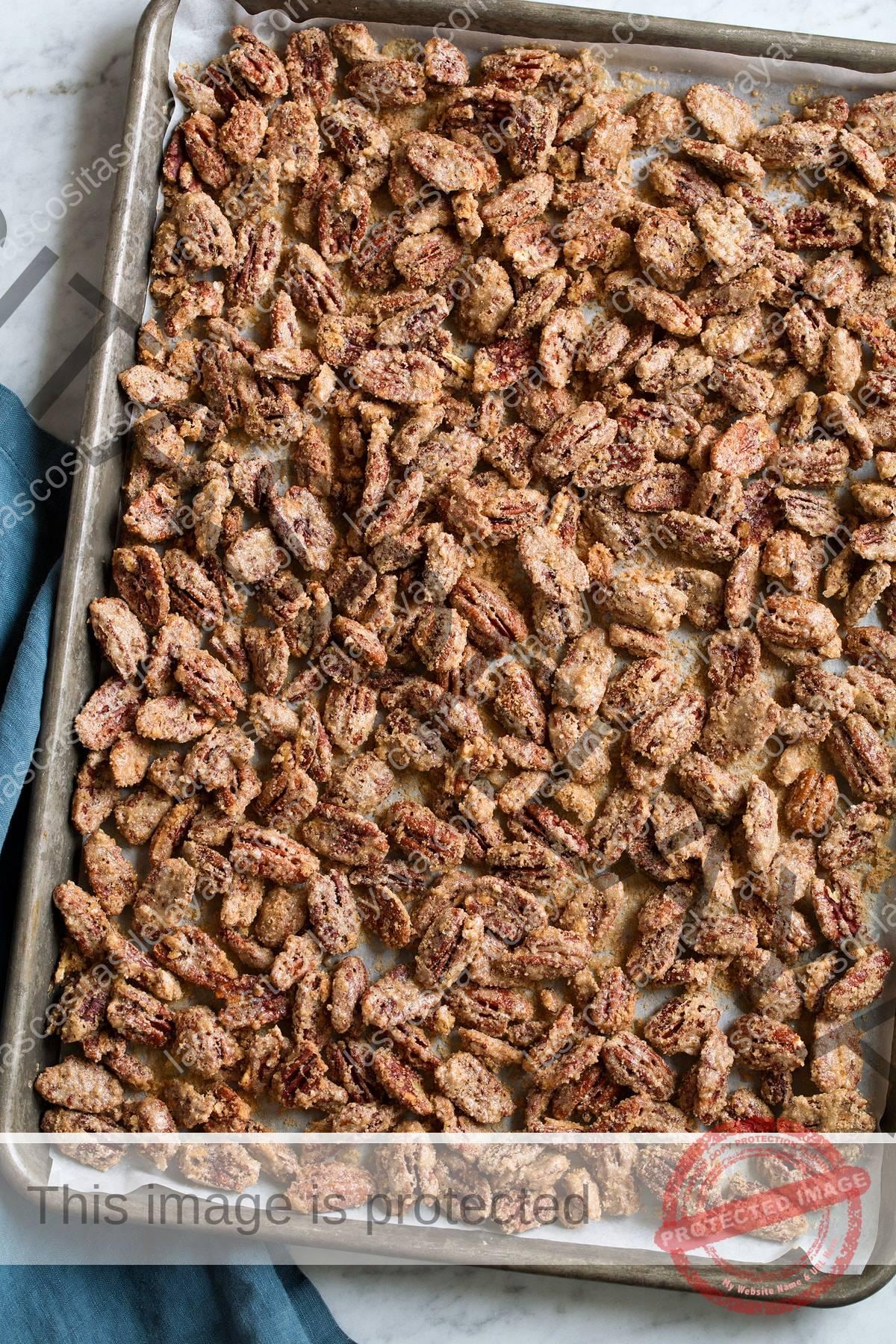 Nueces confitadas terminadas en una bandeja para hornear forrada con papel pergamino.