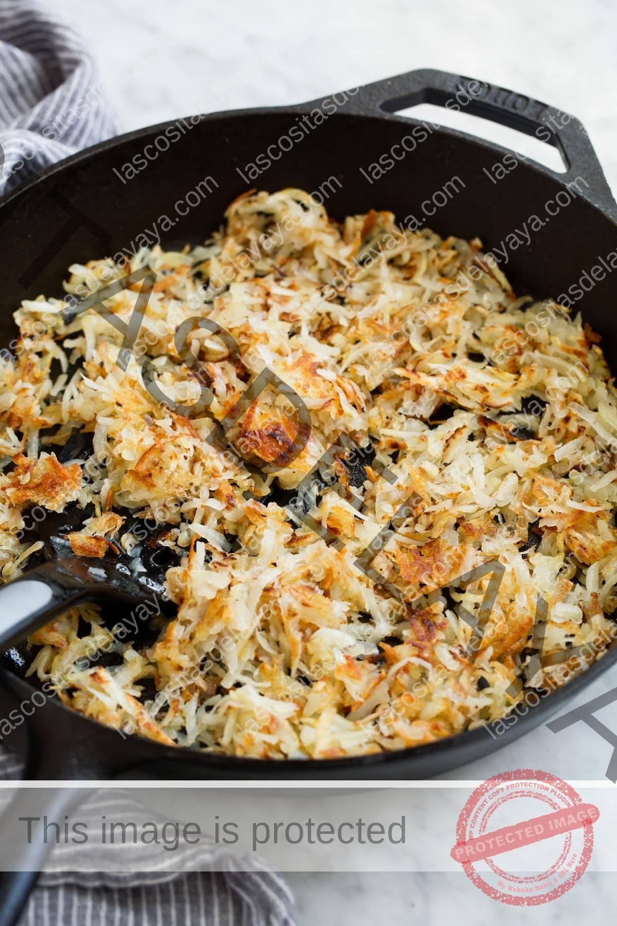 Patatas fritas picadas cocidas en una sartén de hierro fundido.