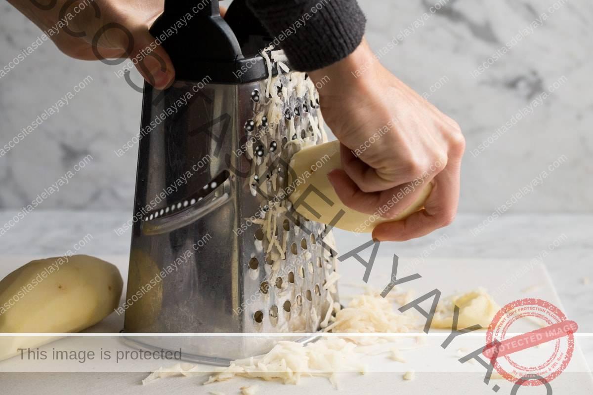 Mostrando cómo hacer papas fritas.  Rallar patatas en los agujeros grandes de un rallador de caja sobre una tabla de cortar.
