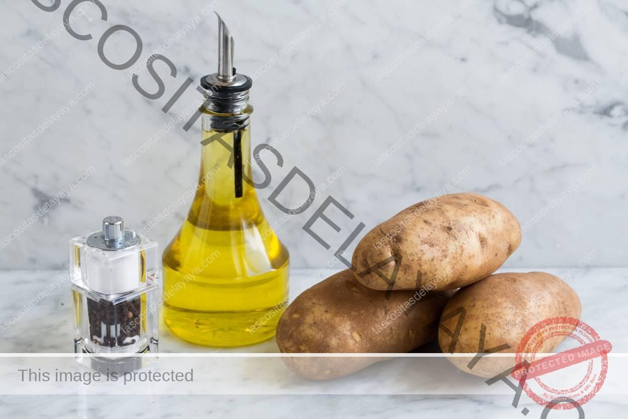 Los ingredientes necesarios para hacer croquetas de patata que se muestran aquí, incluidas las patatas russet, aceite de oliva, sal y pimienta.