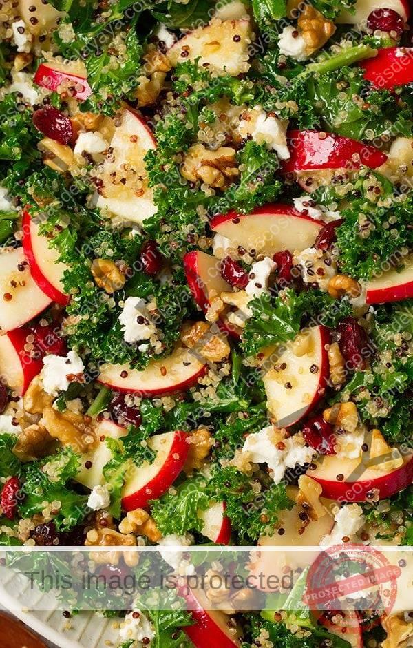 Cerrar imagen de ensalada de col con manzanas, quinoa, queso de cabra y frutos secos.