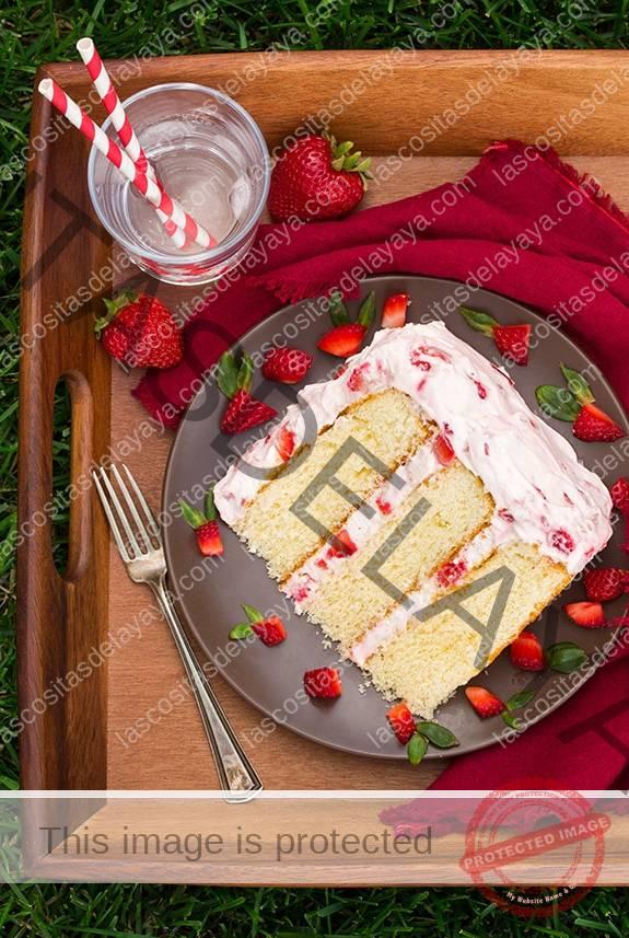 Rebanada de tarta de fresas frescas en un plato con un tenedor y un vaso