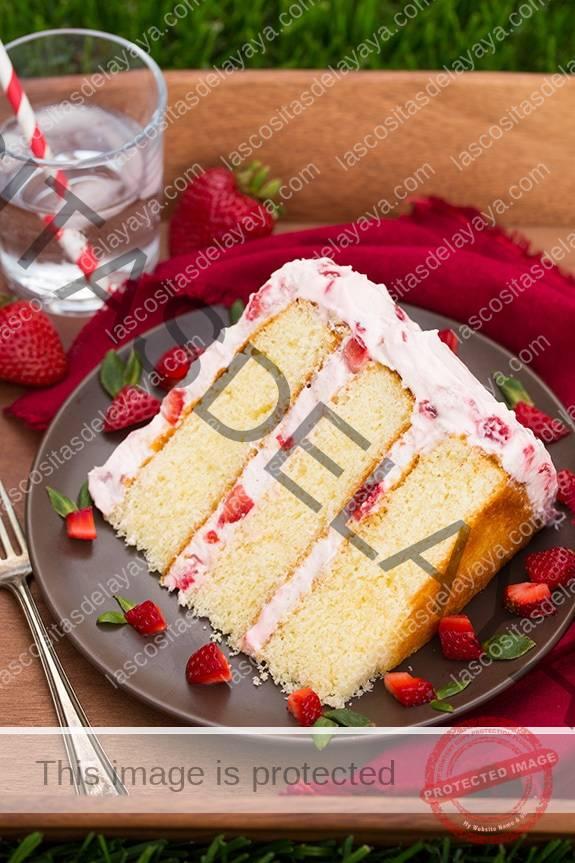 Rebanada de tarta de fresas frescas en un plato con fresas cortadas