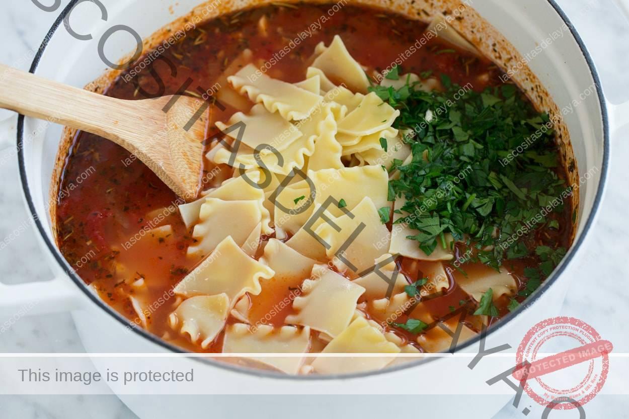 Revuelva los fideos de lasaña cocidos rotos y el perejil en la sopa de lasaña.