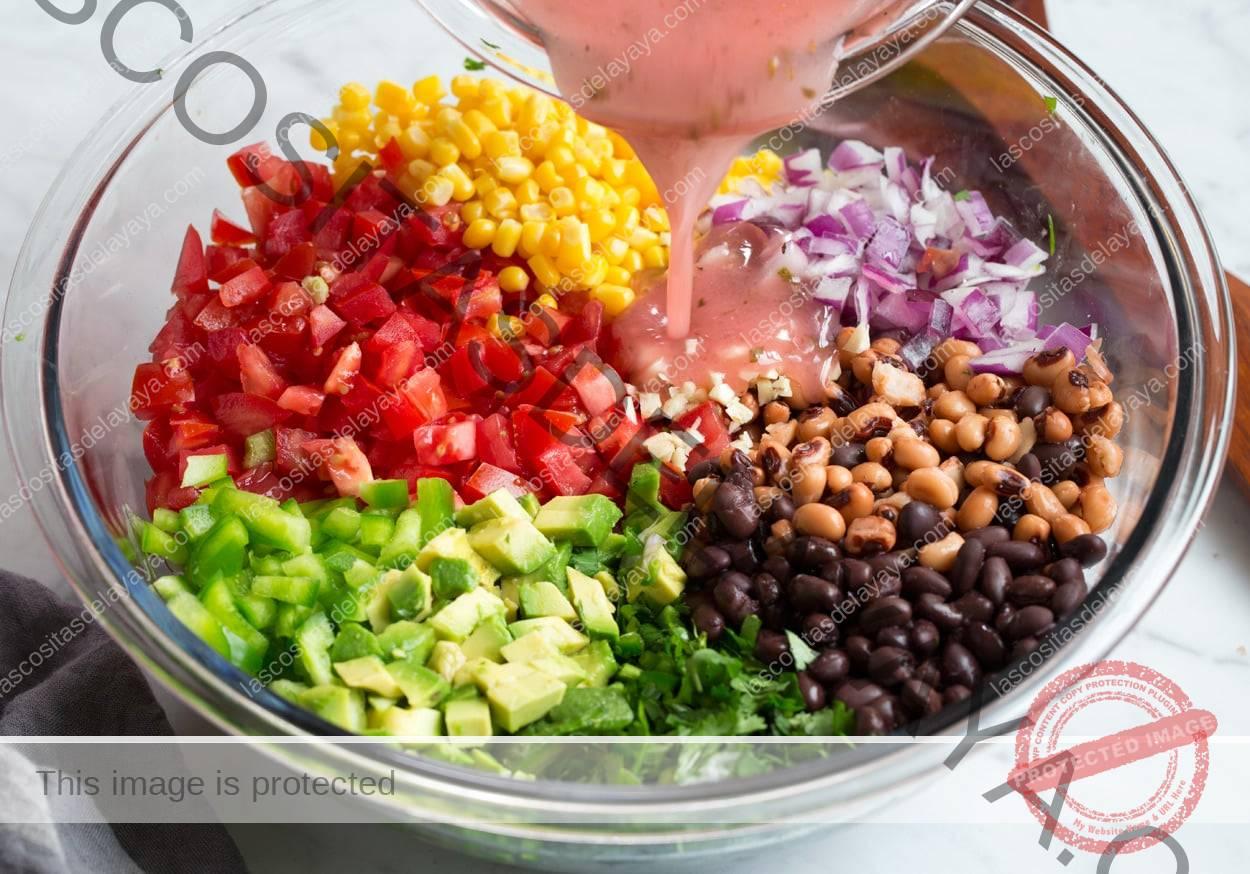 Caviar de vaquero añadiendo salsa a verduras y frijoles en el recipiente
