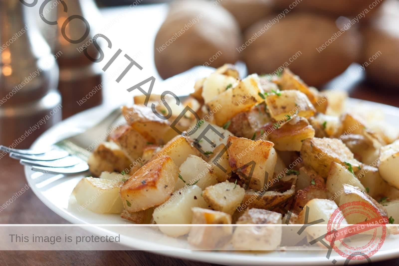 patatas de desayuno perfectamente doradas y crujientes y se muestran en un plato para servir.