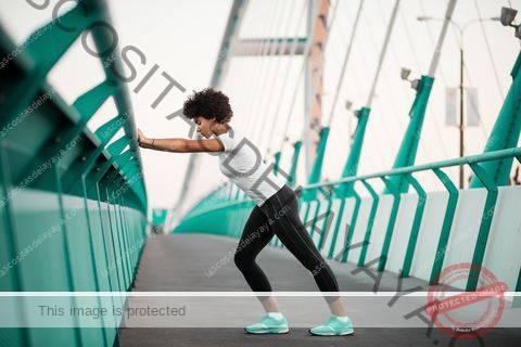atlético, mujer joven haciendo ejercicio en el puente de la ciudad