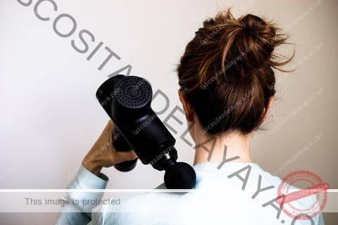 Vista trasera de una mujer con máquina de pistola de masaje