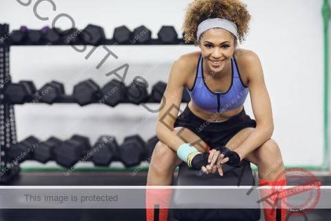 Retrato de feliz atleta femenina sentada en un banco en el gimnasio