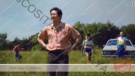 Steven Yeun (centro) se muestra en una escena de & quot; Minari & quot;  con (desde la izquierda) Alan S. Kim, Noel Cho y Yeri Han.