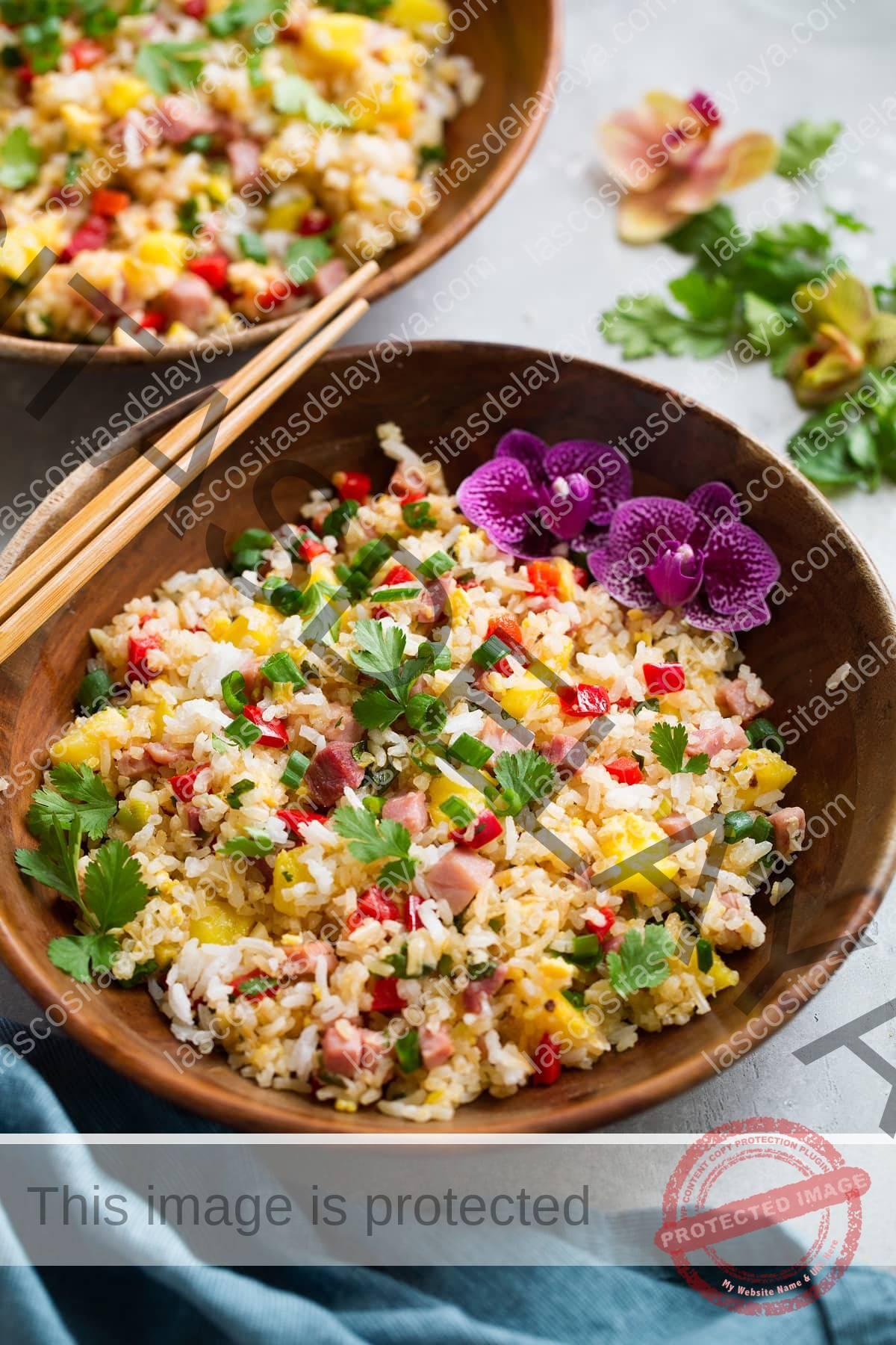 Cuenco de madera lleno de arroz frito hawaiano decorado con flores y palillos en el lateral.