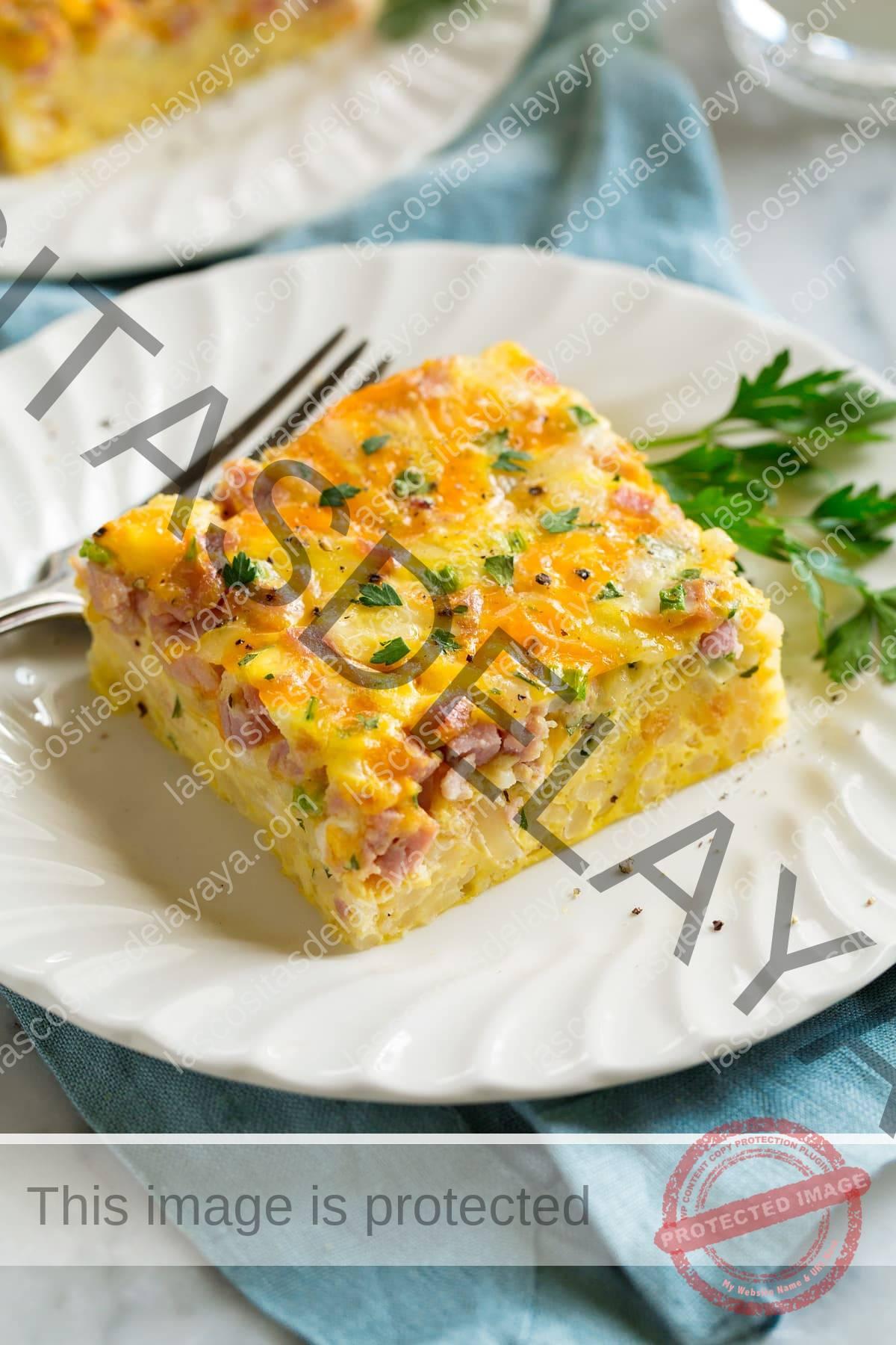 Rebanada de cazuela de desayuno llena de huevos, patatas fritas, jamón y queso en un plato blanco.